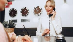 Woman behind a hotel reception desk with a phone to her ear while smiling toward a guest on the other side of the desk