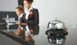 Close up of a service bell sitting atop a black marble reception desk with two female hotel staff working on guest communications through the hotel's software system.