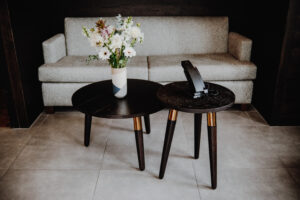 Shot of a coffee table and side table arranged next to each other in front of a cream colored couch