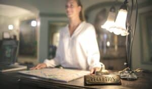 A boutique hotel reception desk with a metal reception sign on a wood block in focus, and a woman smiling away from the camera presumably toward entering guests in the background