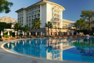 Exterior shot of a luxury resort overlooking a circular pool with the hotel façade in the background