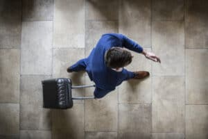 A shot from above looking down on top of a man in blue suit rolling his suitcase through a tiled hallway