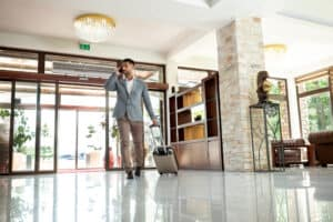 A hotel lobby shot showing a male guest in blazer and slacks rolling a suitcase toward the camera
