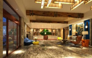 Shot of a spacious inerior hotel lobby and reception area with off-white walls and wood flooring; dark wood beams accent the ceiling.