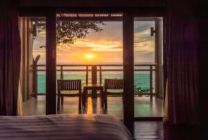 Shot from the interior of a hotel room looking out on a sunset view and bedroom balcony