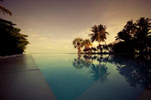 tropical sunset swimming pool scene with palm tree silhouettes