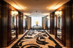 Shot of an interior hotel hallway decorated with a long cream rug with black floral accents between dark wood walls with mirrored insets