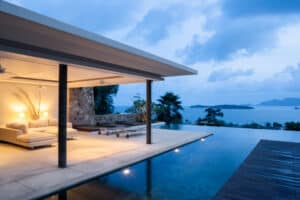 Luxury island hotel looking over an infinity pool at dusk.