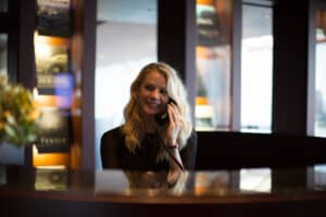 A smiling hotel receptionist talks on her managed voice supported phone to a hotel guest