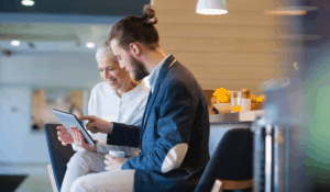 Man and woman sitting in a lobby area reading a tablet about SIP trunking