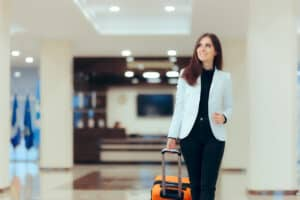 Woman in blue blazer rolling an orange suitcase through a hotel lobby that uses managed voice software for guest communications