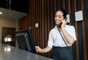 Young latin american receptionist logging a booking into the system while talking on phone smiling